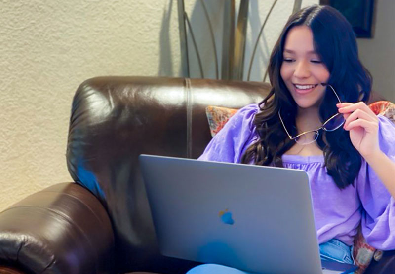 female student sitting on sofa looking at laptop