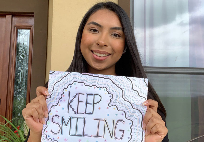 female student holding a keep smiling sign