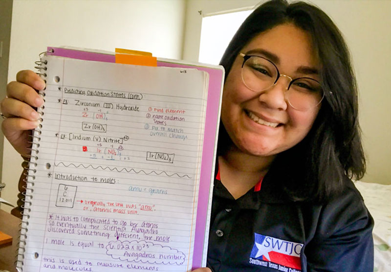 female student holding notebook with written notes